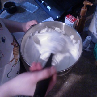 Folding the flour/sugar into the meringue. Wearing my cat apron.