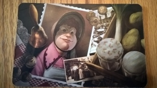 I cannot figure out this woman's profession. She's wearing a bonnet, has potatoes, leeks, and a bell, random coins, and a picture of a group of women in Edwardian dress. We were divided between cook and schoolteacher. Any thoughts?